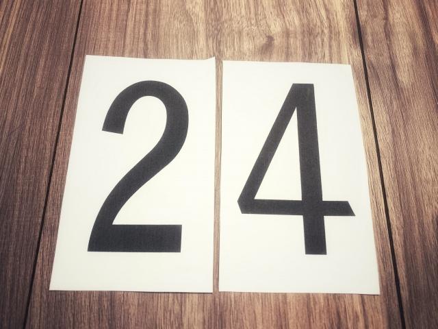 紙に書かれた数字の24が板の上に乗っている